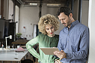 Man and woman looking at tablet in office - RBF05582