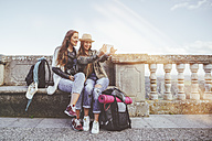 Two happy young women on a trip taking a selfie with a tablet - KIJF01114