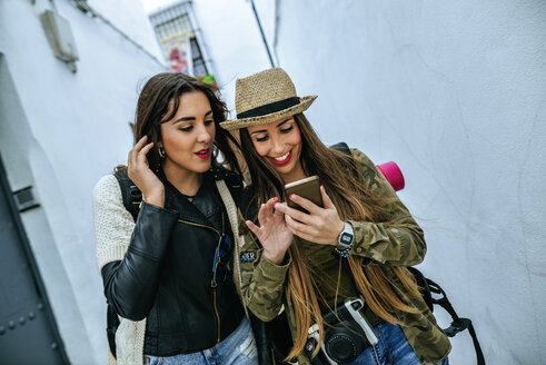 Two young women in a town looking at cell phone - KIJF01123