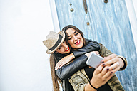 Two happy young women taking a selfie with a smart phone - KIJF01129