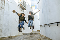 Two happy young women jumping in an alley of a town - KIJF01135