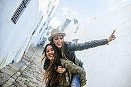 Happy young woman giving friend a piggyback ride - KIJF01138
