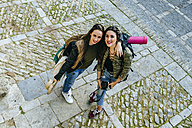 Two traveling young women standing on tow square - KIJF01162