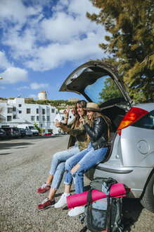 Young women taking a selfie sitting in the trunk of a car. - KIJF01165