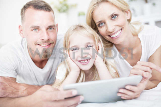 Portait of smiling girl with parents lying in bed with tablet - WESTF22533