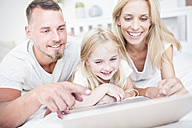 Smiling girl with parents lying in bed using laptop - WESTF22536
