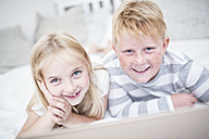 Portait of smiling brother and sister lying in bed with laptop - WESTF22539
