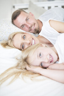 Portait of smiling girl and parents lying in bed - WESTF22551