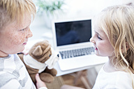 Brother and sister with cuddly toy looking at each other in front of laptop - WESTF22557