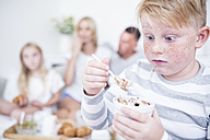 Boy staring at cereal bowl with family in background - WESTF22569