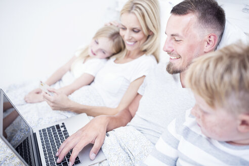 Family lying in bed using laptop - WESTF22572