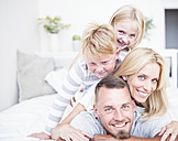 Portrait of smiling family lying in bed on top of each other - WESTF22575
