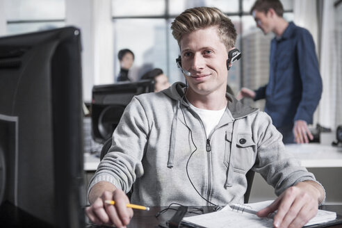 Young man at desk in office wearing a headset - ZEF12494