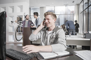 Young man at desk in office wearing a headset - ZEF12497