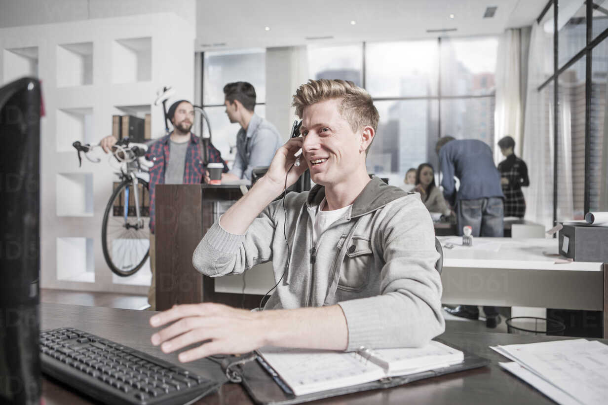 Young man at desk in office wearing a headset - ZEF12497 - zerocreatives/Westend61