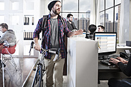 Casual man with bike in modern office - ZEF12503