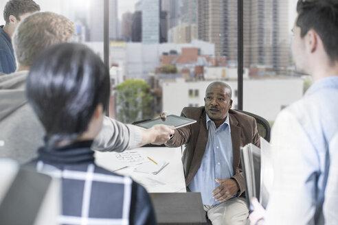 Businessman handing over digital tablet in office - ZEF12509