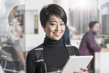 Portrait of smiling woman holding a tablet in office - ZEF12515