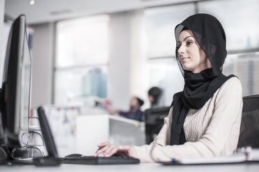 Young woman wearing hijab working on desk in office - ZEF12536