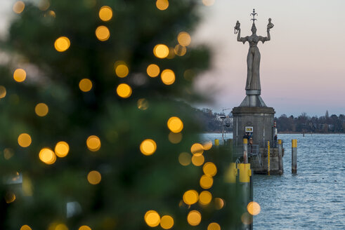 Germany, Baden-Wuerttemberg, Constance, Christmas tree and Imperia statue at harbor - KEB00451