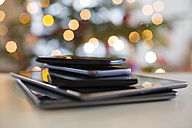 Stack of digital tablets and smartphones at Christmas time, close-up - SARF03131