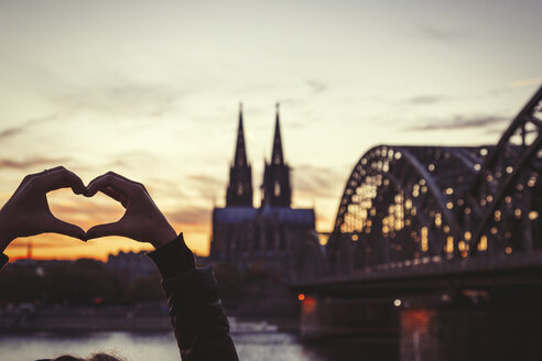 Germany, Cologne, woman shaping heart with her hands in front of Cologne Cathedral and Hohenzollern Bridge at dusk - JUNF00775