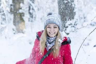Portrait of smiling young woman in heavy snowfall - JUNF00778