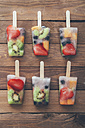 Two row of six fruit ice lollies with fresh fruits on wood - RTBF00609