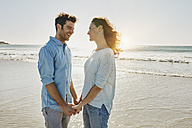Happy couple holding hands on the beach - RORF00544