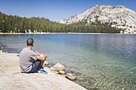 USA, California, Yosemite National Park, man sitting at mountain lake - EPF00297