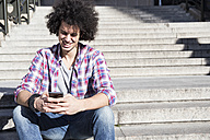 Portrait of smiling young man sitting on stairs looking at cell phone - ABZF01794