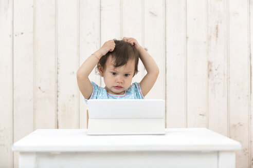 Portrait of little girl tearing her hair out while looking at laptop - DRF01719