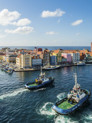 Curacao, Willemstad, Punda, tugboats and colorful houses at waterfront promenade - AMF05226