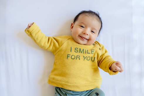 Happy baby girl smiling on the bed - GEMF01457