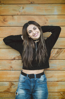 Portrait of smiling young woman standing in front of wooden wall with hands behind head - RAEF01676