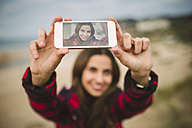 Photography of young woman taking a selfie on display of smartphone - RAEF01685