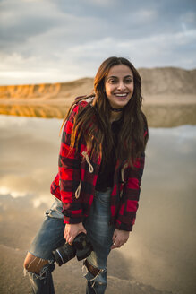 Portrait of smiling young woman with camera on the beach - RAEF01688