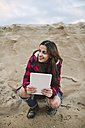 Young woman with tablet crouching on the beach - RAEF01691
