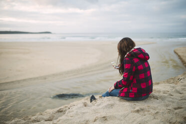 Young woman on the beach looking at cell phone - RAEF01694