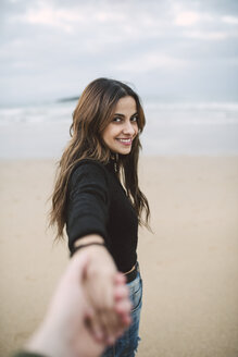 Portrait of happy young woman holding hand on the beach - RAEF01697
