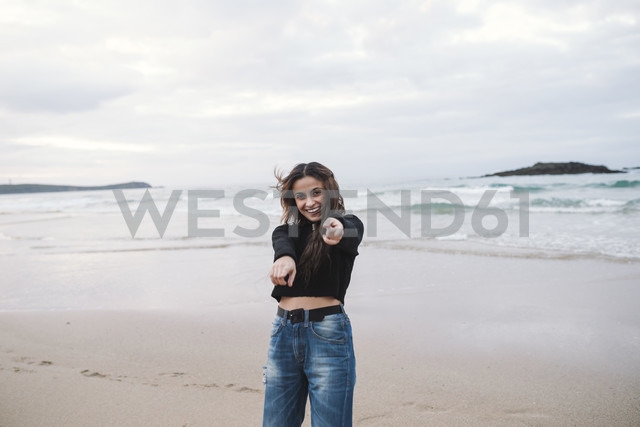 Portrait of happy young woman on the beach pointing on viewer - RAEF01700 - Ramon Espelt/Westend61