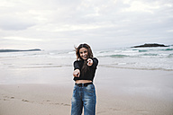 Portrait of happy young woman on the beach pointing on viewer - RAEF01700