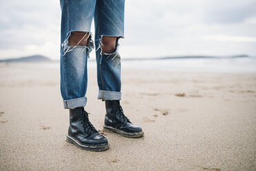 Woman wearing boots and torn jeans  on the beach, partial view - RAEF01703