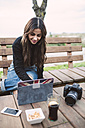 Young woman using tablet in outdoor cafe - RAEF01706