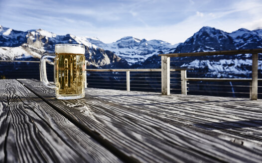 Switzerland, Portes du Soleil, Champery, mug of beer on rustic tabletop - FMKF03482