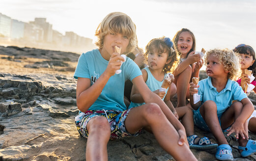 Group of six children eating icecream on the beach - MGOF02820