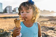 Portrait of little girl eating chocolate icecream on the beach at sunset - MGOF02823