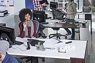 Smiling woman at desk in office thinking - ZEF12578
