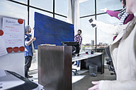 Two men positioning painting together in office - ZEF12584