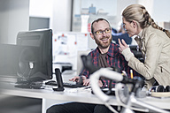 Woman talking to smiling colleague at desk in office - ZEF12593